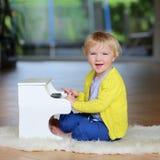 小小孩女孩弹玩具钢琴 免版税库存照片