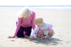 一起使用在海滩的祖母和孙女 免版税库存照片