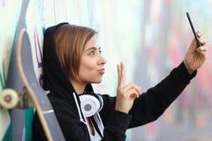 溜冰者拍摄与聪明的电话照相机的少年女孩一张照片 库存照片