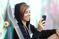 年轻使用一个巧妙的电话的溜冰者愉快的青少年的女孩 免版税图库摄影
