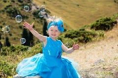有泡影吹风机的可爱的小孩女孩在草甸的草 夏天绿色自然背景 免版税库存图片