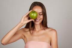 Το νέο όμορφο προκλητικό κορίτσι με τη σκοτεινή σγουρή τρίχα, τους γυμνούς ώμους και το λαιμό, που κρατούν το μεγάλο πράσινο μήλο Στοκ Φωτογραφίες
