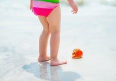 在女婴的特写镜头发现了在海岸的壳 库存照片