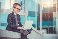 与膝上型计算机的孩子商人 库存图片