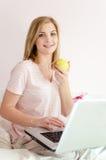 吃苹果美丽的柔和的甜少妇画象在床上与膝上型计算机看照相机的个人计算机计算机 免版税库存图片