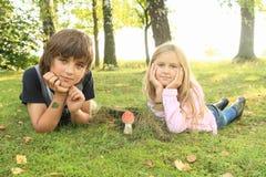 与红色伞菌的两个孩子 免版税库存照片