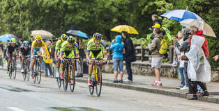 乘坐在雨中的小组骑自行车者 免版税库存图片