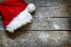 在葡萄酒木板圣诞节背景的圣诞老人帽子 库存图片
