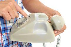 拨号在一个轮循拨号电话的年轻人 免版税库存图片