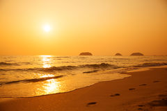 在美好的海运日落之上 在沙子的脚印 免版税库存图片
