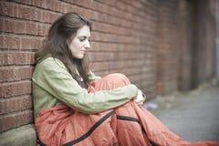 睡觉在街道上的脆弱的十几岁的女孩 库存图片
