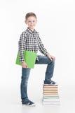 有书的愉快的男小学生在白色背景 免版税库存图片