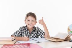 坐在桌和写上的逗人喜爱的男孩 库存图片