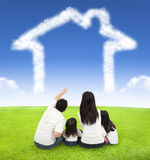 愉快的家庭坐有云彩房子的一个草甸  免版税库存照片