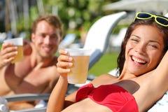 在放松的人饮用的啤酒在海滩胜地 免版税库存图片