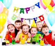 小组笑的孩子获得乐趣在生日聚会 库存图片