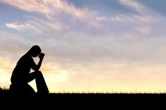 坐下在祷告剪影的妇女 免版税库存图片