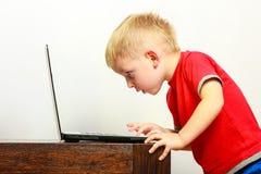 在家使用膝上型计算机个人计算机计算机的小男孩 免版税库存照片