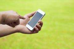 触摸屏手机在手中有绿色草甸的 免版税图库摄影
