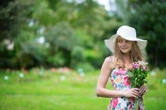 拿着花的白色帽子的女孩 免版税库存图片