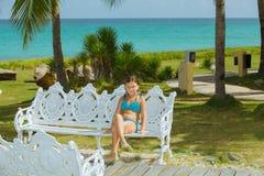 泳装的愉快的女孩享受她的业余时间的通过坐老牌金属长凳 免版税图库摄影