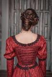 红色礼服的美丽的中世纪妇女,后面 免版税库存照片