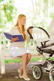 有书和婴儿推车的愉快的母亲在公园 免版税库存图片