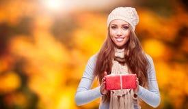 拿着在秋天背景的愉快的妇女礼物 免版税库存照片