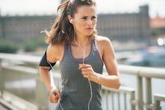 跑步在城市的健身少妇 免版税库存图片