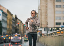 跑步在多雨城市的健身少妇 免版税库存图片