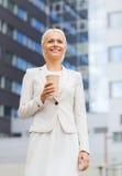 有纸杯的微笑的女实业家户外 免版税库存图片