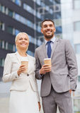 与纸杯的微笑的商人户外 免版税图库摄影