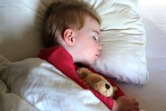 Ύπνος κοριτσιών μικρών παιδιών στο κρεβάτι Στοκ Φωτογραφίες
