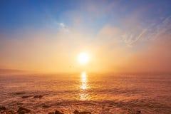 在有雾的海的日出 免版税库存照片