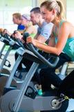 在转动在体育自行车的健身房的小组 免版税库存照片