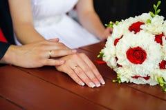 爱接触 婚礼夫妇手在有花束的手上 免版税库存图片