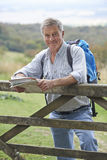 步行在乡下的老人休息由门 免版税库存照片