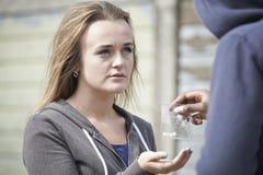 在街道上的十几岁的女孩买的药物从经销商 库存照片