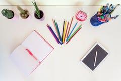 打开练习本、铅笔蜡笔和片剂在白色书桌上 库存图片