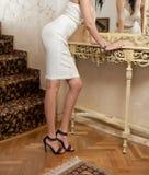 短的白色紧的调查镜子的适合裙子和束腰的美丽的少妇 在镜子前面的完善的身体女性 免版税库存照片