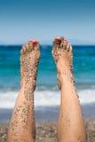 悬而未决女性含沙的脚 库存照片