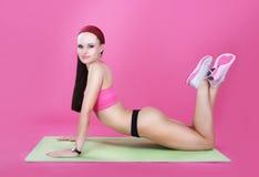 普拉提 体育俱乐部的苗条年轻女运动员 免版税库存照片