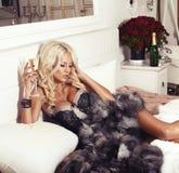 说谎在床上的女用贴身内衣裤和皮大衣的性感的白肤金发的妇女用香槟 免版税图库摄影