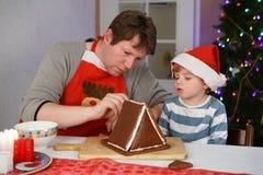 Πατέρας και λίγος γιος που προετοιμάζουν ένα σπίτι μπισκότων μελοψωμάτων Στοκ Φωτογραφία