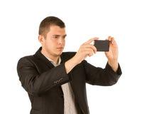 拍与他的手机的年轻人一张照片 免版税库存图片
