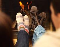 一对夫妇的腿在袜子的在壁炉前面在冬天晒干 免版税图库摄影