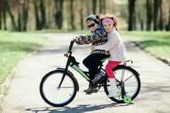 在一起自行车的小女孩和男孩骑马 免版税库存图片