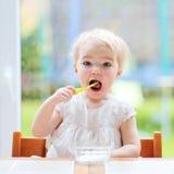 Χαριτωμένο κοριτσάκι που τρώει το γιαούρτι από το κουτάλι Στοκ εικόνα με δικαίωμα ελεύθερης χρήσης