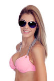 有太阳镜和桃红色比基尼泳装的可爱的时尚妇女 免版税库存图片