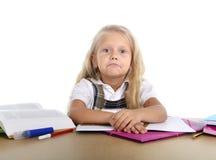 甜矮小的学校女孩疲倦了和哀伤在与书和家庭作业的重音 图库摄影